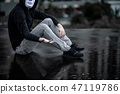 Mystery man in white mask sitting in the rain 47119786