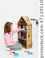 Happy girl plays with cardboard doll house. Funny lovely child is having fun. 47120510