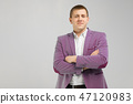 young man in a jacket folded arms isolated on light background 47120983