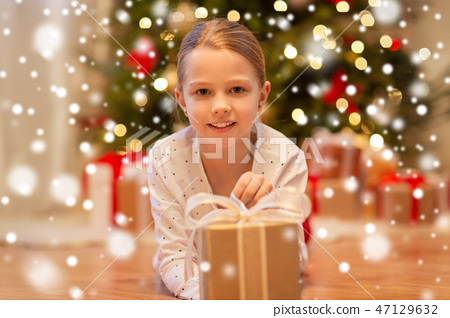 smiling girl with christmas gift at home 47129632