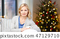 middle aged woman over christmas thee lights 47129710