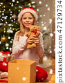 smiling girl in santa hat with christmas gift 47129734