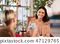 female friends drinking coffee and talking at cafe 47129765
