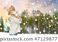 happy woman in hat and scarf over winter forest 47129877