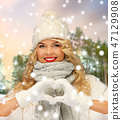 happy woman in winter clothes showing hand heart 47129908