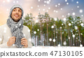 smiling man in hat and scarf over winter forest 47130105