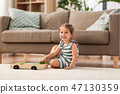 happy baby girl playing with toy blocks at home 47130359