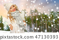 happy woman in hat and scarf over winter forest 47130393