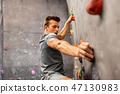 young man exercising at indoor climbing gym 47130983