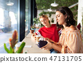 female friends paying for coffee at cafe 47131705