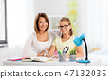 mother and daughter doing homework together 47132035
