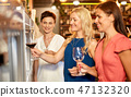 happy women pouring wine from dispenser at bar 47132320