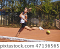 a Girl playing tennis on the court on a beautiful sunny day 47136565