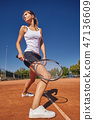 a Girl playing tennis on the court on a beautiful sunny day 47136609