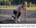 a young woman runner getting ready for a run on track 47136765