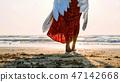 Beautiful female angel walking barefoot toward the sea at sunset. 47142668