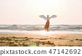 Beautiful female angel walking barefoot toward the sea at sunset. 47142692
