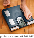 Measuring  weight using body scale 47142942