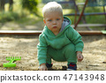 Cute blonde toddler playing in sandbox with a toy 47143948