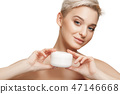 Cute girl preparing to start her day. She is applying moisturizer cream on face. 47146668