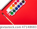 Watercolor paints and brushes with canvas for painting with copyspace on red background 47148683