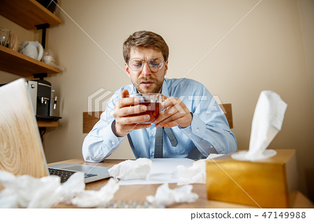 Sick man while working in office, businessman caught cold, seasonal flu. 47149988