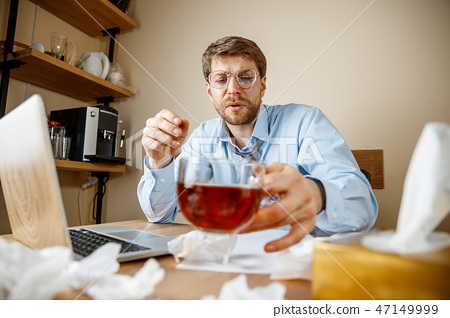 Sick man while working in office, businessman caught cold, seasonal flu. 47149999