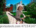 Little cheerful blonde girl riding a scooter on paved paths on a sunny summer day 47154147