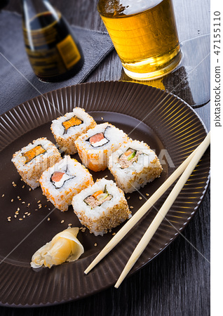 Sushi on a brown plate with a glass of beer, soy s 47155110