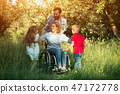 Children run to their disabled mother in the park 47172778