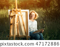 Woman in wheelchair drawing on easel outside 47172886