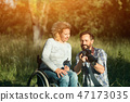 Disabled woman look on the taken photos on camera. 47173035