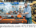 Salesman is posing with woodworking machine  47173072