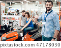 Salesman is posing with couple of clients and keys 47178030