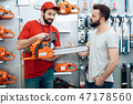 Salesman is showing bearded client new chainsaw  47178560