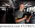 A cheerful senior man in gym measuring time while doing exercise. Copy space. 47178971