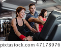 Two cheerful female seniors in gym with a young trainer doing cardio work out. 47178976