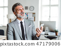 Cheerful mature businessman with smartphone standing in an office, laughing. 47179006