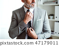 A midsection of mature businessman standing in an office, holding a tie. 47179011