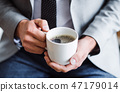 A midsection of businessman sitting in an office, holding a cup of coffee. 47179014