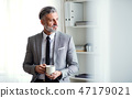 A mature businessman standing in an office, holding a cup of coffee. Copy space. 47179021