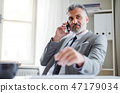 Serious mature businessman with smartphone sitting at the table, making a phone call. 47179034