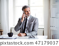 Serious mature businessman with smartphone sitting at the table, making a phone call. 47179037