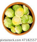 Fresh Brussels sprouts in wooden bowl over white 47182557