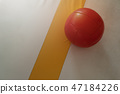 Row of red heavy balls in the corner of the room 47184226