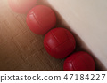 Row of red heavy balls in the corner of the room 47184227