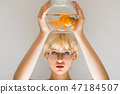 Portrait of a beautiful girl with a goldfish in an aquarium. 47184507