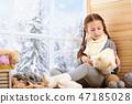 Child girl sitting on window sill with wool yarns 47185028