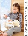 Child girl sitting on window sill with wool yarns 47185031