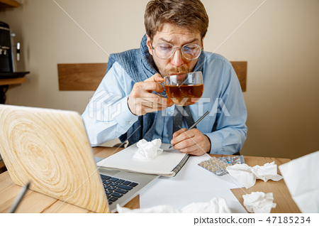 Sick man while working in office, businessman caught cold, seasonal flu. 47185234